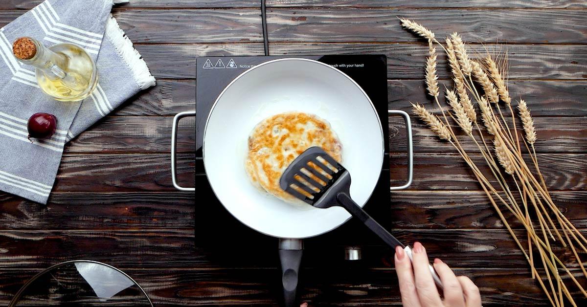 Шаруваті коржі з цибулею на сковороді